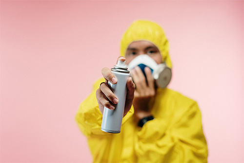 Man in a hazmat suit with a respirator mask holding an unmarked aerosol spray can